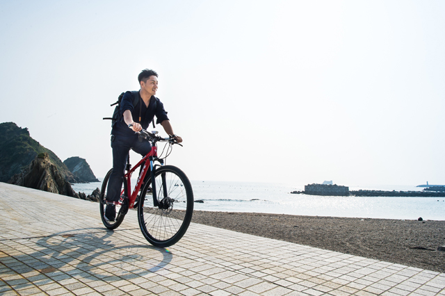 Chef Imamura at the seaside on a bicycle