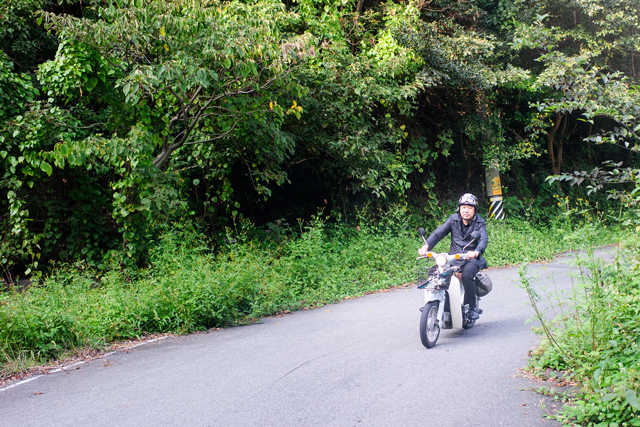 Chef Kawase riding the Super Cub on a mountain road