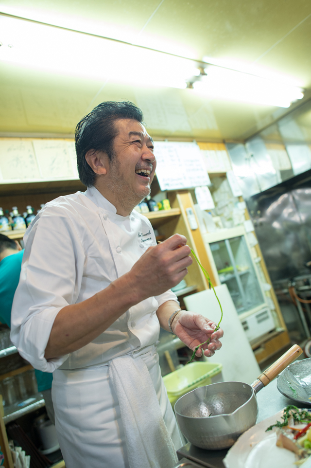 Chef Kawase laughing at the fishermen's talk as he cooks
